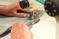 Os processos de costura na máquina de costura costuram a máquina de costura das mãos das mulheres Imagem de Stock Royalty Free