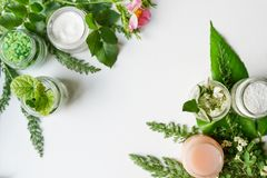 Os produtos cosméticos, as folhas e as flores do corpo facial florescem no espaço desktop branco da cópia do whith do fundo dispo imagem de stock royalty free
