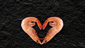 Os produtos do mar, coração deram forma ao camarão, fundo preto no de volta a para escrever seu artigo imagem de stock royalty free