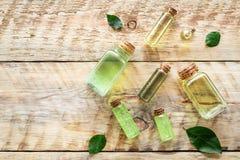 Os produtos dos cuidados com a pele com árvore do chá lubrificam em umas garrafas no copyspace de madeira rústico do teste padrão imagem de stock royalty free