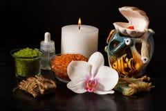 Os produtos dos termas e a orquídea branca florescem no fundo preto Fotografia de Stock Royalty Free