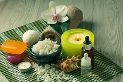 Os produtos dos termas na orquídea de madeira do fundo florescem, rolam com mar Fotografia de Stock