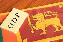 Os produtos internos da palavra ou o GDP bruto escritos no papel na bandeira de Sri Lanka imagem de stock royalty free