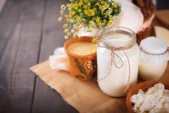 Os produtos láteos sortidos ordenham, iogurte, requeijão, creme de leite Ainda vida rústica Foto de Stock Royalty Free