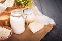 Os produtos láteos sortidos ordenham, iogurte, requeijão, creme de leite Ainda vida rústica Fotos de Stock