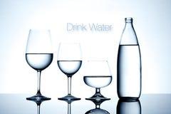 Os produtos vidreiros e a garrafa encheram-se com água no fundo branco Imagem de Stock