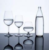 Os produtos vidreiros e a garrafa encheram-se com água no fundo branco Fotos de Stock Royalty Free