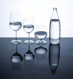 Os produtos vidreiros e a garrafa encheram-se com água no fundo branco Fotos de Stock