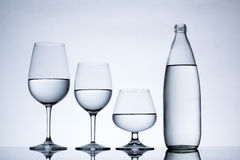 Os produtos vidreiros e a garrafa encheram-se com água no fundo branco Foto de Stock Royalty Free