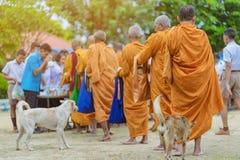 Os professores e os estudantes fazem junto o m?rito para dar ofertas do alimento a uma monge budista em dias religiosos important imagens de stock royalty free