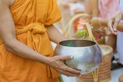 Os professores e os estudantes fazem junto o m?rito para dar ofertas do alimento a uma monge budista em dias religiosos important fotos de stock