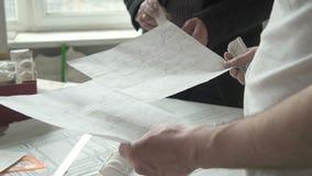 Os profissionais dos arquitetos estão trabalhando no projeto da restauração que está na oficina moderna vídeos de arquivo