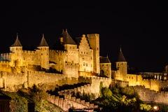 Os projectores iluminam a entrada aos ramparts e às torres da fortaleza medieval em Carcassonne. Imagem de Stock