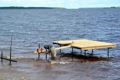 Os projetos do metal de soldas do trabalhador de um cais no reservatório de Rybinsk Região de Yaroslavl fotografia de stock royalty free