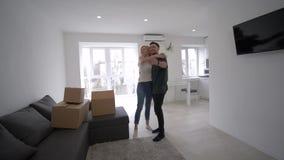 Os proprietários de casa novos felizes homem e mulher levam caixas e a casa nova da compra do prazer durante a festa de inaugura vídeos de arquivo