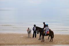 Os proprietários e os cavalos na praia esperam visitantes Imagem de Stock