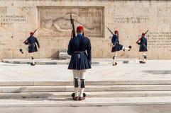 Os protetores cerimoniais presidenciais de Evzones guardam o túmulo do soldado desconhecido na construção grega do parlamento fotos de stock royalty free