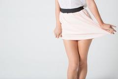 Os pés das mulheres em uma saia Imagem de Stock