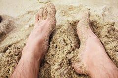 Os pés de um homem na praia Foto de Stock