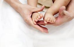 Os pés do bebê do bebê de um ano da posse das mãos do pai fecham-se acima sobre o branco Fotos de Stock