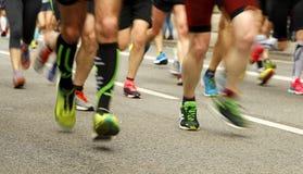 Os pés dos corredores na estrada no borrão fazem sinal Imagem de Stock Royalty Free