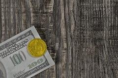 Os punhados de cem notas de dólar e um dólar do ouro da parte superior em um fundo de madeira imagem de stock