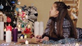Os punhos da menina tiram uma imagem um adolescente que encontra-se no assoalho, tirando um desenho para Santa Claus perto da video estoque