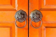 Os punhos do ` dos leões penduram em uma porta do chinês tradicional foto de stock royalty free