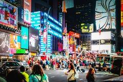 Os quadros de avisos de propaganda maciços elevam-se acima do tráfego e dos pedestres na interseção entre o Times Square e o Broa Foto de Stock