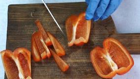 Os quartetos da pimenta vermelha estão sendo cortados para partes menores pelo chefe video estoque