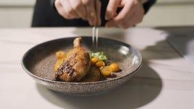 Os quartos do pé de galinha Roasted com pele marrom dourada friável serviram com salada fresca filme