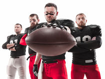 Os quatro jogadores de futebol americano que levantam com a bola no fundo branco imagens de stock royalty free