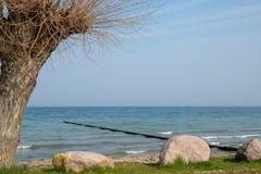 Os quebra-mar longos projetam-se na água do mar Báltico azul fotografia de stock