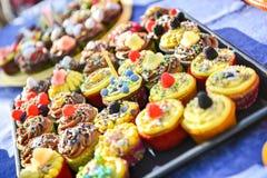 Os queques coloridos deliciosos com uma vela do aniversário estão em um plat Fotos de Stock