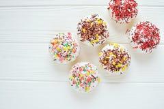 Os queques com creme branco e polvilham no fundo branco Imagens de Stock