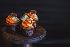 Os queques com creme em um vidro escuro, decorado com chocolate, biscoitos estão em um suporte da madeira escura em um fundo escu Imagens de Stock