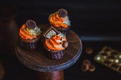 Os queques com creme em um vidro escuro, decorado com chocolate, biscoitos estão em um suporte da madeira escura em um fundo escu Foto de Stock Royalty Free