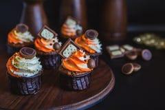 Os queques com creme em um vidro escuro, decorado com chocolate, biscoitos estão em um suporte da madeira escura em um fundo escu Fotografia de Stock