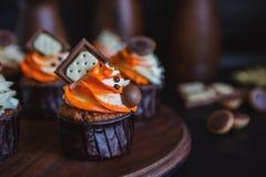 Os queques com creme em um vidro escuro, decorado com chocolate, biscoitos estão em um suporte da madeira escura em um fundo escu Fotos de Stock Royalty Free