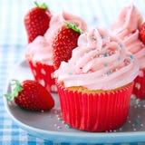 Os queques cor-de-rosa com morangos frescas e polvilham Imagem de Stock