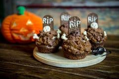 Os queques de Dia das Bruxas com lápide endurecem o chapéu de coco e candle em uma tabela de madeira velha foto de stock royalty free