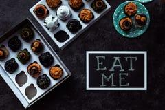 Os queques de Dia das Bruxas e comem-me inscrição Imagem de Stock Royalty Free