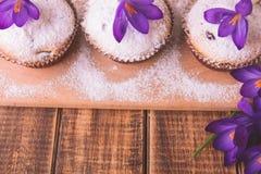 Os queques decorados com açafrão florescem na luz de madeira - fundo roxo Imagens de Stock