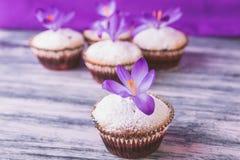 Os queques decorados com açafrão florescem na luz de madeira - fundo roxo Foto de Stock Royalty Free