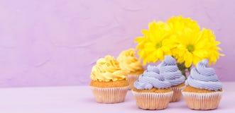 Os queques decorados com creme e o ramalhete amarelos e violetas dos crisântemos no fundo pastel violeta com área de texto para c Fotografia de Stock