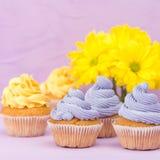 Os queques decorados com creme e o ramalhete amarelos e violetas dos crisântemos no fundo pastel violeta com área de texto para c Imagem de Stock Royalty Free