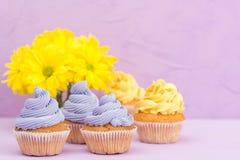 Os queques decorados com creme e o ramalhete amarelos e violetas dos crisântemos no fundo pastel violeta com área de texto para c Foto de Stock