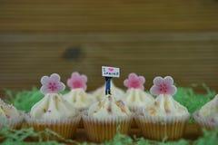Os queques deliciosos do buttercream cobriram com formas cor-de-rosa congeladas da flor e uma estatueta diminuta da pessoa com si Imagens de Stock Royalty Free