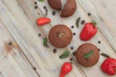 Os queques do chocolate com morango Mint as folhas sobre o deserto rústico de Gray Background Breakfast imagem de stock royalty free