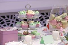 Os queques e os macarons doces estão na tabela Fotografia de Stock Royalty Free